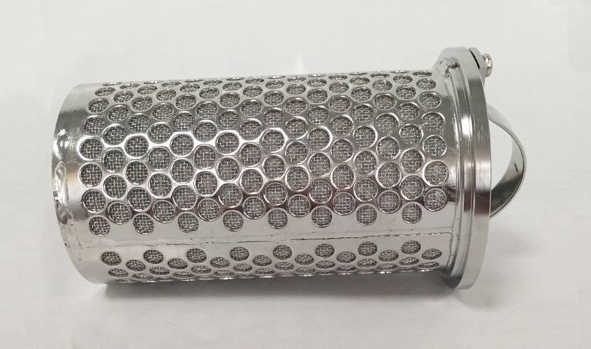 A perforated metal sintered filter basket is lying on the gray background.