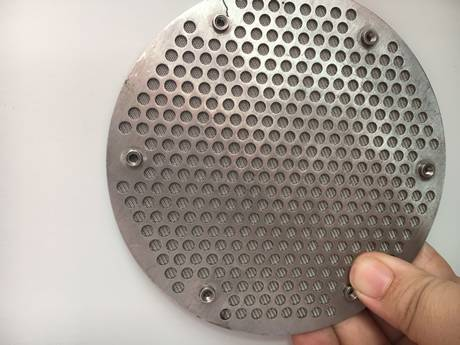 A hand is holding a round shape perforated metal sintered filter disc.